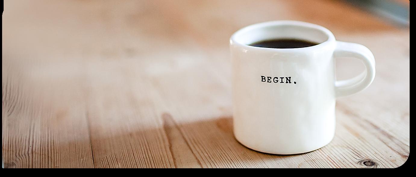 Tasse de café ou est écrit begin dessus, posée sur une table